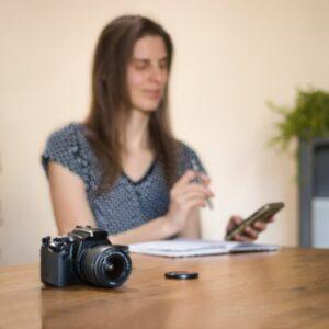 žena sedící u stolu, kde leží foťák